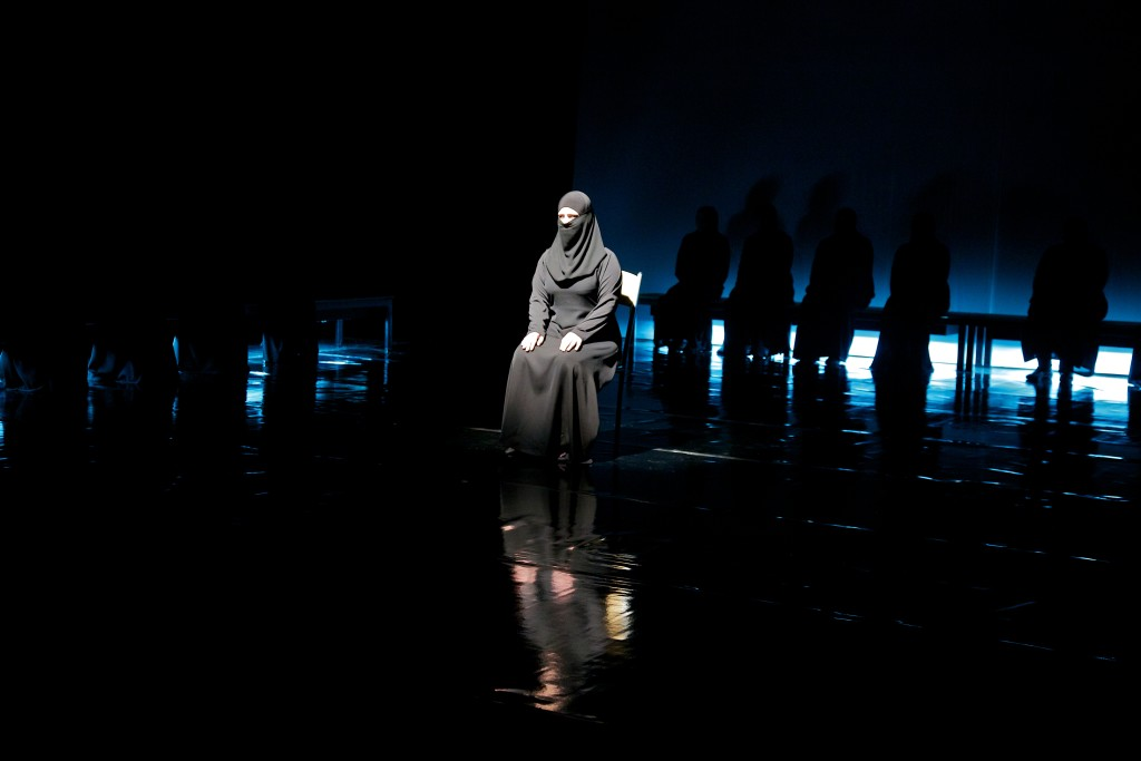 A woman shares a story about her escape from Syria during the performance.